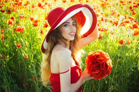 woman with long curly hair in red dress and retro hat hold flower bouquet in field of poppy seed on sunny natural background, summer, drug and love intoxication, opium, pin up woman Stock Photo
