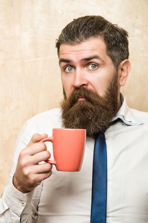 男でも長いひげとネクタイで驚いた顔でスタイリッシュな髪とリフレッシュメントとエネルギー、朝のコーヒー カップからお茶を飲む質感のベージ 写真素材