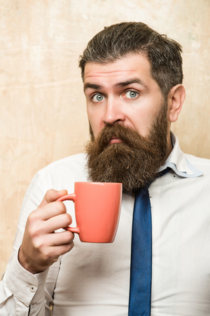 man or businessman with long beard and stylish hair on surprised face in tie and white shirt on textured beige background drink tea from coffee cup, morning and energy, refreshment