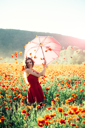 pretty happy girl with long curly hair in red dress hold pink umbrella in field of poppy seed flower on green stem with petal in sky on natural background, summer, drug and love intoxication, opium
