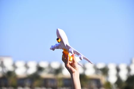 Het vervoervak speelgoedmodel van Aairplane in vrouwelijke hand op natuurlijke onduidelijk beeldachtergrond en blauwe hemel openlucht