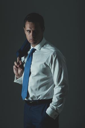 ビジネスマンやファッショナブルな白いシャツ、青いネクタイと灰色の背景上の肩にジャケットでポーズをとって成功したマネージャー。ビジネス