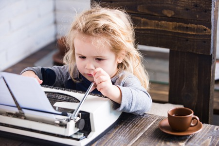 boy or small kid with typewriter, paper and coffee cup working at table