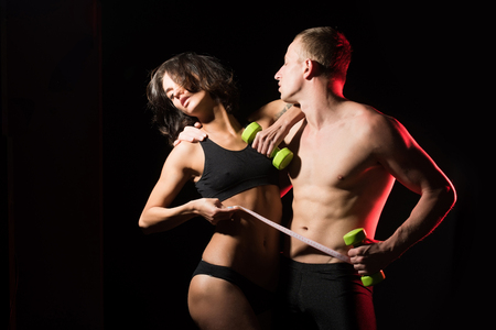 athletic couple of sexy woman and man with muscular body and torso hold dumbbell or barbell in hands and tape measure, sport and fitness, coach, workout, dieting and health Stock Photo
