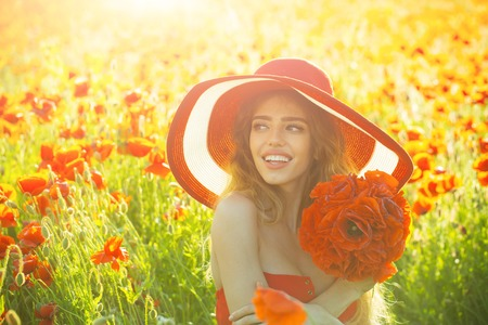 infatuation: flower bouquet at smiling girl with long curly hair in red dress and retro hat in field of poppy seed on sunny natural background, summer, drug and love intoxication, opium, pin up woman