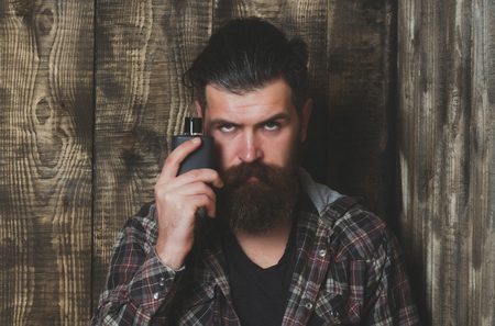 Bearded man or brutal caucasian hipster with grey hair, long beard and moustache posing with black perfume or cologne bottle on wooden background. Male fragrance and perfumery. Cosmetics