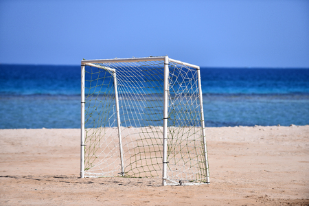 Goal soccer. Goalpost on sand beach on background of blue sea and sky in summer