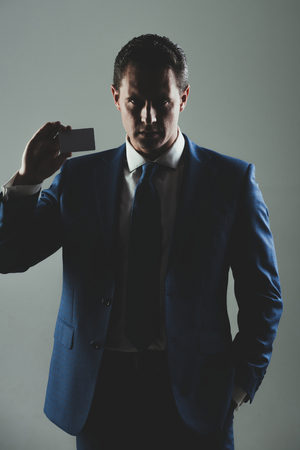 man, businessman or manager holding bank or business card in stylish blue formal suit and tie on grey background. Shadow business and economy, banking, fraud, skimming, ecash and information
