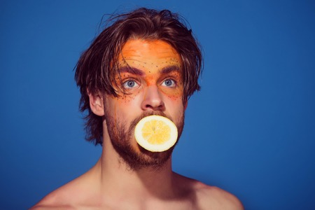 lemon and man. handsome surprised guy with creative fashionable makeup on face hold fruit in mouth on blue background, beauty and fashion, allergy, healthcare and vitamin, vegetarian and dieting Stock Photo