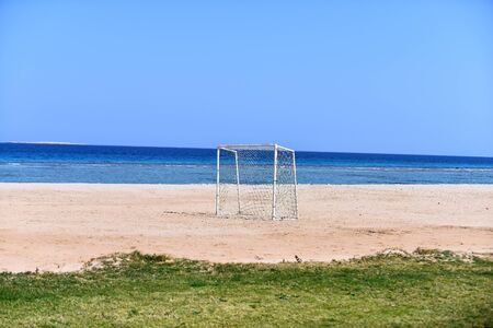 White goal soccer on the beach blue sky background. Gate football on the coast.