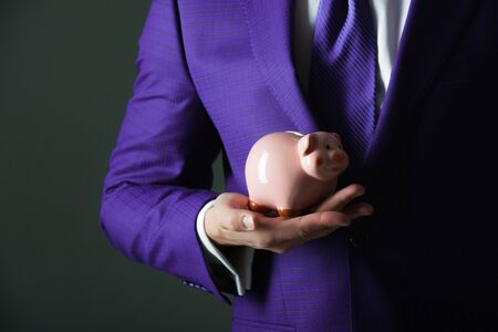Pink piggy bank for saving money standing on male hand. Fashionable violet formal suit and tie on grey background. Business, banking, moneybox and credit 版權商用圖片 - 81150676