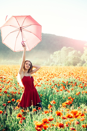 pretty happy girl with long curly hair in red dress hold pink umbrella in field of poppy seed flower on green stem on natural background, summer, drug and love intoxication, opium