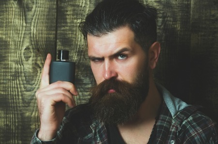 hipster or brutal caucasian man with grey hair, long beard and moustache posing with black perfume or cologne bottle on wooden background. Male fragrance and perfumery. Cosmetics