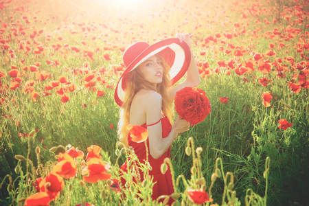girl with long curly hair in red dress and retro hat hold flower bouquet in field of poppy seed on sunny natural background, summer, drug and love intoxication, opium, pin up woman Stock Photo