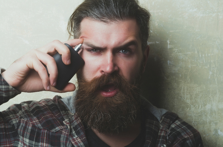 Surprised bearded man or caucasian hipster applying perfume or cologne from black bottle on face with open mouth, long beard and moustache on grey background. Male fragrance and perfumery. Cosmetics