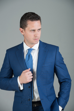 businessman, confident man or successful boss with stylish hair, haircut posing in fashionable violet formal suit jacket, white shirt and tie on grey background. Business, fashion and success