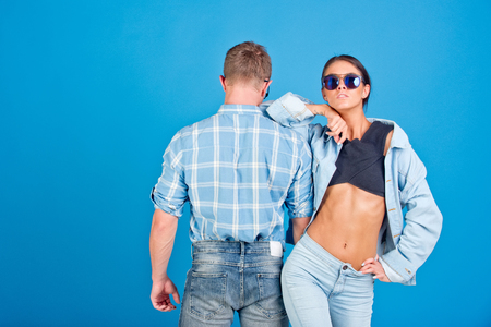 サングラス、シャツとジーンズとスタイリッシュな男女のカップルは、青色の背景色、デニム スタイル、美容、ファッション、夏、学生のライフ ス