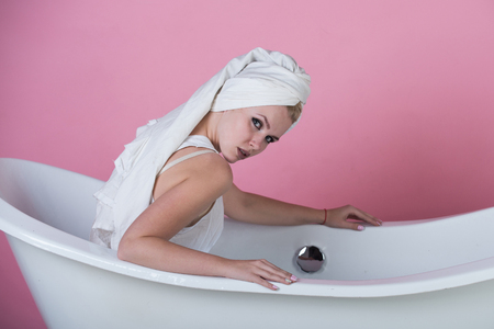 spa and beauty, pretty sexy woman with towel turban on head sitting in white bathtub on pink background, relax and hygiene, healthcare and housekeep