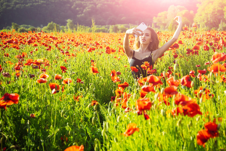 selfie photo by mobile phone of girl with long curly hair in black vest in flower field of red poppy seed with green stem on natural background, summer, spring, drug and love intoxication, opium Stock Photo