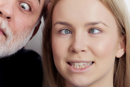funny bearded man: Girl and man squinting eyes on silly faces. Young woman with crossed grey eyes and makeup foundation and old male with white beard. Grimace. Strabismus