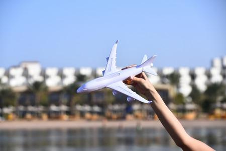Wit vliegtuig modelvervoer in vrouwelijke hand op achtergrond van blauwe hemel en water, die over reis, vervoersconcept dromen
