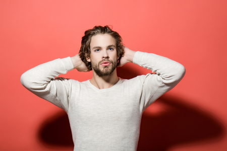 handsome man with beard and stylish hair in white underwear with raised hands on red background, morning and fashion