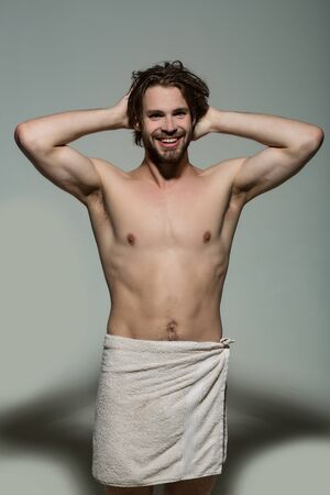 happy man with beard and long hair in white towel on grey background, morning wake up and shower