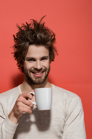 cup of tea or coffee at happy man with uncombed hair in underwear on red background, morning refreshment and drink, energy Stock Photo