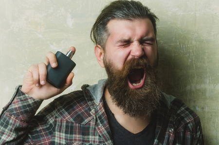 hipster or brutal bearded man with long beard and moustache screaming with closed eyes while applying perfume or cologne from black bottle on grey wall. Male fragrance and perfumery. Cosmetics