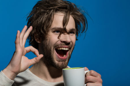 uncombed: ok gesture of happy man with cup of tea or coffee has uncombed hair in underwear on red background, morning refreshment and drink, energy