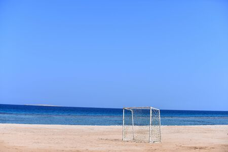 Soccer goal sport construction with net on beach on background of blue sky, sea and natural horizon in summer, copy space