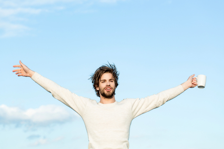 energy and freedom, happy man with cup of tea or coffee has uncombed hair in underwear on sky background outdoor, morning refreshment and drink, energy