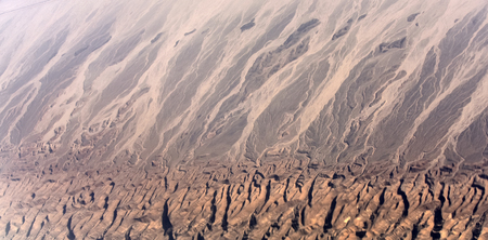 Desert with brown rugged terrain and sand barchan dunes from airplane flight on natural background, geology and geographic concept