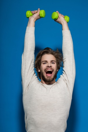 uncombed: happy man. guy with barbell or dumbbell workout, has disheveled and uncombed long hair and beard on face in white underwear on blue background, morning exercise and wake up, barbershop, sport Stock Photo