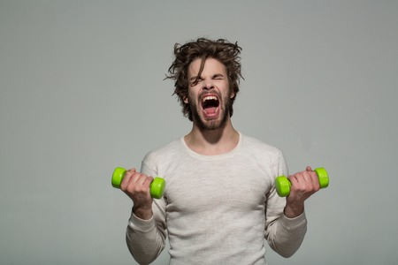 sleepy man with barbell or dumbbell workout, has disheveled and uncombed long hair and beard on yawning face in white underwear on grey background, morning exercise and wake up, barbershop, sport