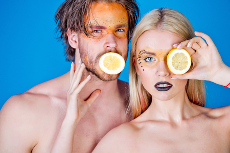 vitamine: woman and man with creative fashionable makeup on face hold lemon fruit on blue background, beauty and fashion, allergy, healthcare and vitamin, vegetarian and dieting, couple in love
