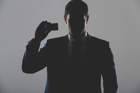 男性、ビジネスマンやマネージャーの持株事業、灰色の背景にブルーのフォーマルなスーツで銀行カードのシルエット。影のビジネス、経済、金融 写真素材