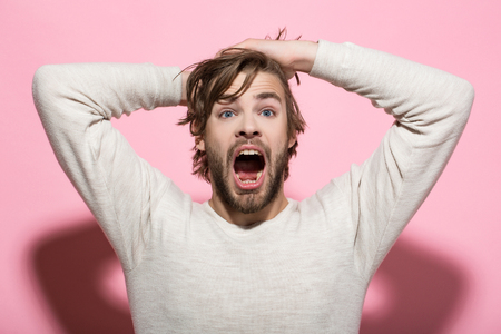 surprised man with disheveled and uncombed long hair with beard on scared face in white underwear on pink background, morning and wake up, everyday life, barbershop Stock fotó