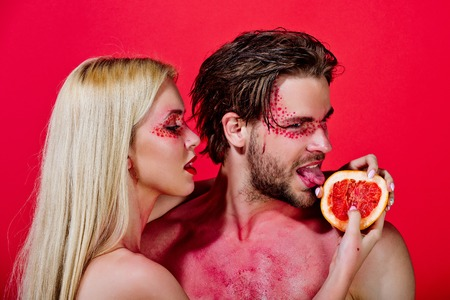 vitamine: couple of woman and man with creative fashionable makeup on face hold grapefruit fruit on red background, beauty and fashion, allergy, healthcare and vitamin, vegetarian and dieting Stock Photo
