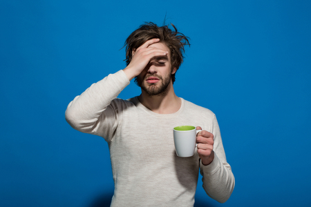 morning. sleepy tired man with headache hold cup of tea or coffee has uncombed hair in underwear on blue background, morning refreshment and drink 스톡 콘텐츠