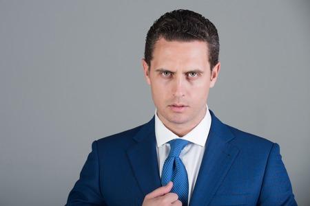 上司にはスタイリッシュな髪、ファッショナブルなフォーマル スーツ ジャケット、白シャツでポーズをとって散髪と灰色の背景に結ぶ。ビジネス、