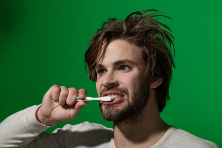 handsome young man brushing his teeth on green background