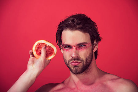 grapefruit in hand of handsome man with creative fashionable makeup on face hold fruit on red background, beauty and fashion, allergy, healthcare and vitamin, vegetarian and dieting Stock Photo