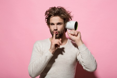 hush gesture of man overhear with cup in morning on pink background