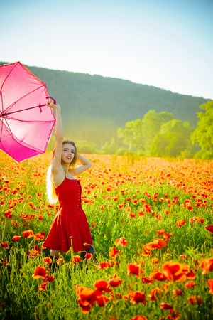 happy girl with the pink umbrella over the poppy field in red dress on natural background
