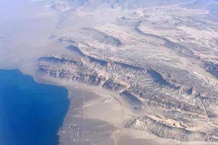 Beautiful landscape with barren terrain desert and coastline with blue water of ocean natural aerial view, summertime and travel concept