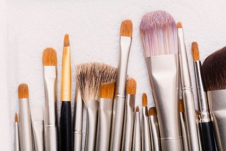 Makeup brushes with natural and synthetic fluff on white background. Make up and cosmetic tool set with silver and black handles for visage. Beauty salon Stok Fotoğraf