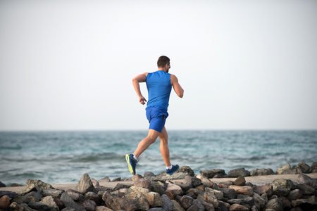 Back view running male athlete boy in blue sportswear with muscular strong body on stone coast of ocean in summer on background of sky and water Banque d'images