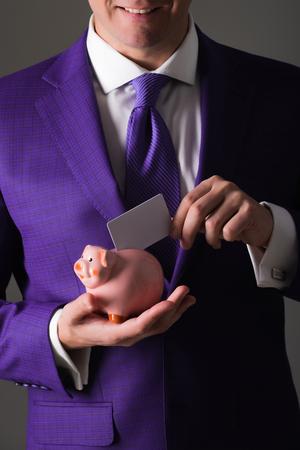 geldbesparingen. handen die leeg adreskaartje in spaarvarken voor besparing op grijze achtergrond zetten. Stijlvol formeel blauw pak en stropdas. Bankieren, geld, lening, spaarpot, ecash en informatie