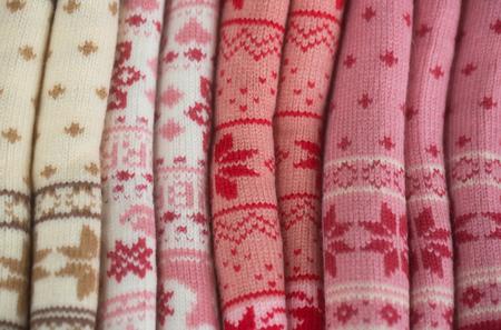 Brei of gebreide collectie met sneeuwvlok patroon gerold op kleurrijke wollen achtergrond. Breien en knitwear. Mode. Warme winterkleren